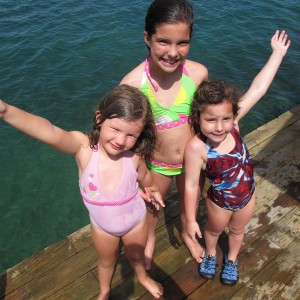 Three girls posing for a photo at the dock